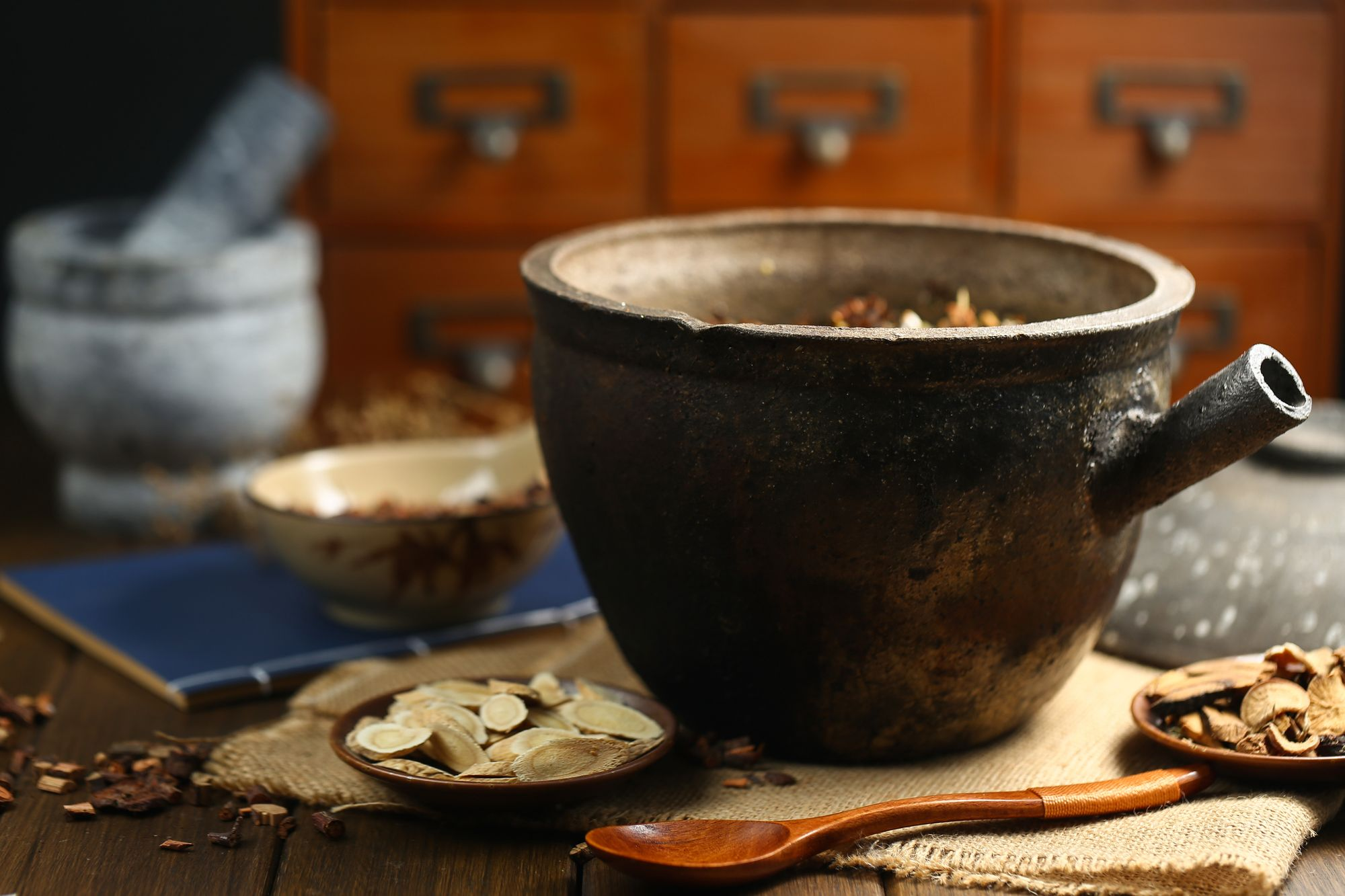 image: Chinese medicine ceramic pot and wooden spoon
