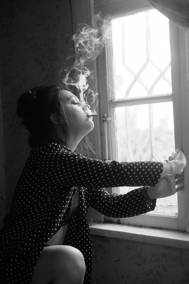 image: woman smoking cannibis by a window relaxing